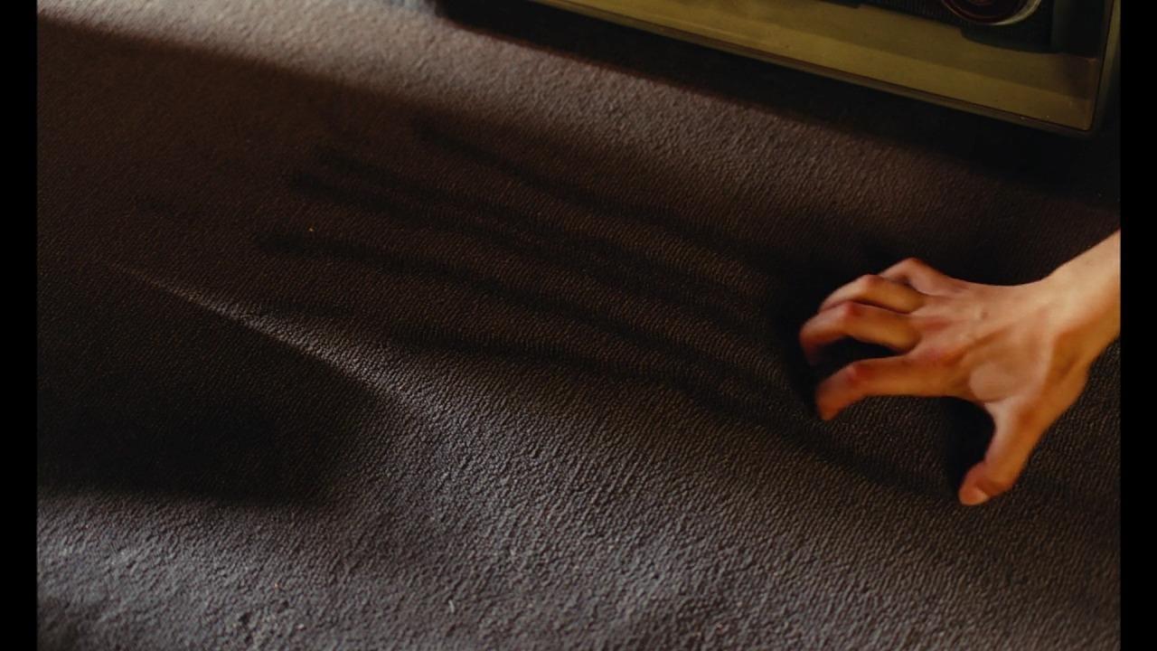 カーペットに爪を立てるシーン