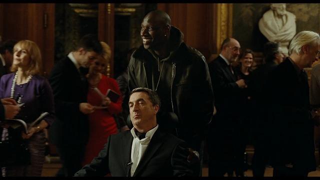 劇場でフィリップの車いすを押すドリス