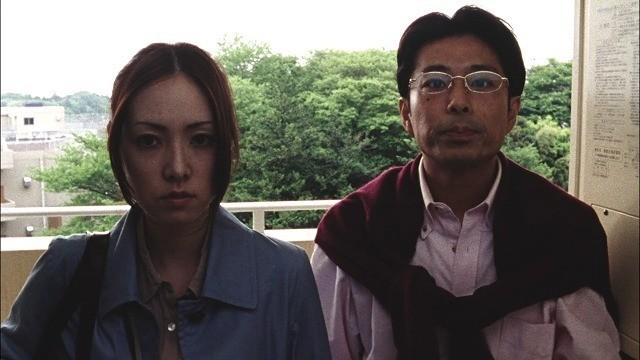 真紀と宮田の同僚が玄関先で待つ